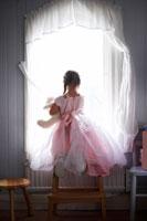 ドレス姿で窓際に座っている女の子