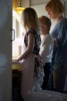 キッチンに立っている親子3人