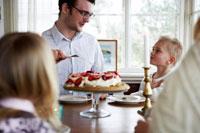 息子にケーキを取り分けるお父さん