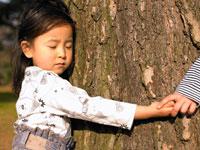 木の周りを手を繋いで囲む子供たち