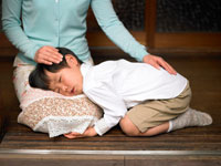 お母さんの膝枕で昼寝をする男の子