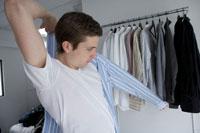 ストライプのワイシャツの袖に腕を通す男性