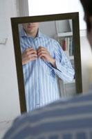 ワイシャツを着る鏡越しの男性