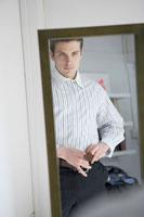 スーツパンツのベルトを締める鏡越しの男性