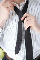 黒いネクタイを締める男性