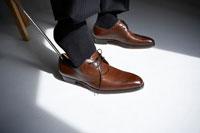 椅子に座って茶色の革靴を履く男性 24014000070| 写真素材・ストックフォト・画像・イラスト素材|アマナイメージズ