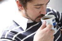 ソファーでコーヒーを飲みながら読書する男性