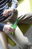 ソファーでビールを飲み時間を確認する男性
