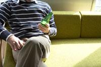 ソファーでビールを飲む男性