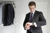 腕時計で時間を確認する男性 24014000107| 写真素材・ストックフォト・画像・イラスト素材|アマナイメージズ