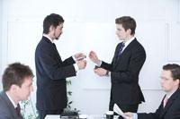 会議室で名刺を交換するビジネスマン