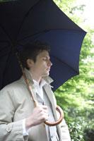 傘をさして森を歩く男性