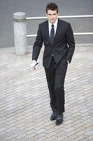 新聞を手に持ち歩道を歩くビジネスマン