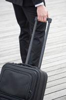 キャリーバッグを運ぶビジネスマン