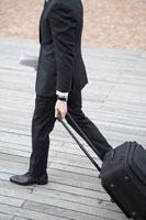 新聞を持ちながらキャリーバッグを運ぶビジネスマン