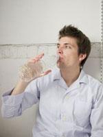 パジャマ姿で水を飲む男性