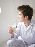 パジャマ姿で牛乳を飲む男性