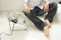 床に座って扇風機の風を浴びる男性