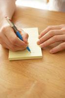 机の上で手紙を書く男性