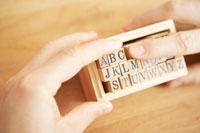 アルファベットのスタンプを手にする男性 24014000384  写真素材・ストックフォト・画像・イラスト素材 アマナイメージズ