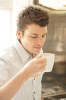 コーヒーの香りをかぐ男性