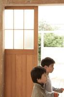扉のそばで横を向く少年2人