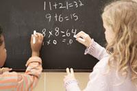 黒板に数式を書く少年少女2人 24014000420| 写真素材・ストックフォト・画像・イラスト素材|アマナイメージズ