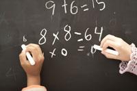 黒板に数式を書く少年少女の手元