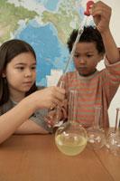 フラスコで実験をする少年少女2人