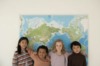 世界地図の前に立つ少年少女4人