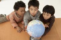 地球儀を見る少年3人