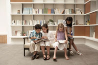 ソファで本を読む少年少女4人