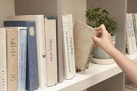 本棚から本を取り出す少女の手元
