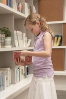 本棚の前で本を読む少女