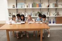 机に並んで本を読む少年少女6人