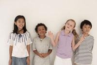 白い壁の前に並ぶ少年少女4人