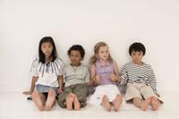 白い壁の前に座る少年少女4人