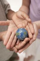 小さな地球ボールを持つ子供の手元 24014000486  写真素材・ストックフォト・画像・イラスト素材 アマナイメージズ