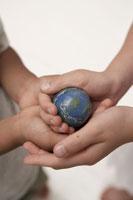小さな地球ボールを持つ子供の手元 24014000487A  写真素材・ストックフォト・画像・イラスト素材 アマナイメージズ