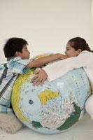 地球儀ボールを抱く少年少女2人