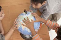 地球儀を覗き込む少年少女3人