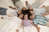 床に寝そべる少年少女7人 24014000520| 写真素材・ストックフォト・画像・イラスト素材|アマナイメージズ