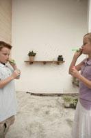 シャボン玉で遊ぶ少年少女2人