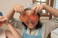 トマトを目にあてる少女2人