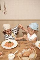 スパゲッティを前にふざける少年少女2人