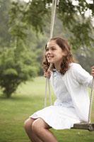 庭でブランコに乗って遊ぶ少女