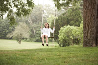 庭でブランコに乗って遊ぶ少女 24014000619  写真素材・ストックフォト・画像・イラスト素材 アマナイメージズ