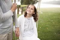 庭でブランコに乗って遊ぶ娘と母