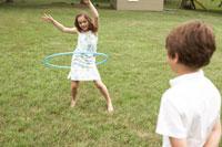庭でフラフープをして遊ぶ少女と少年