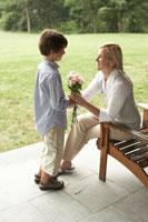 母親に白いバラの花束をプレゼントする息子